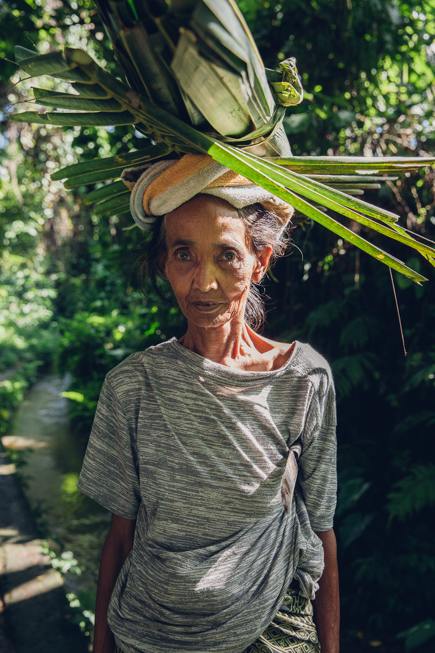 Пожилая женщина несет срезанные листья на голове, Бали, Индонезия