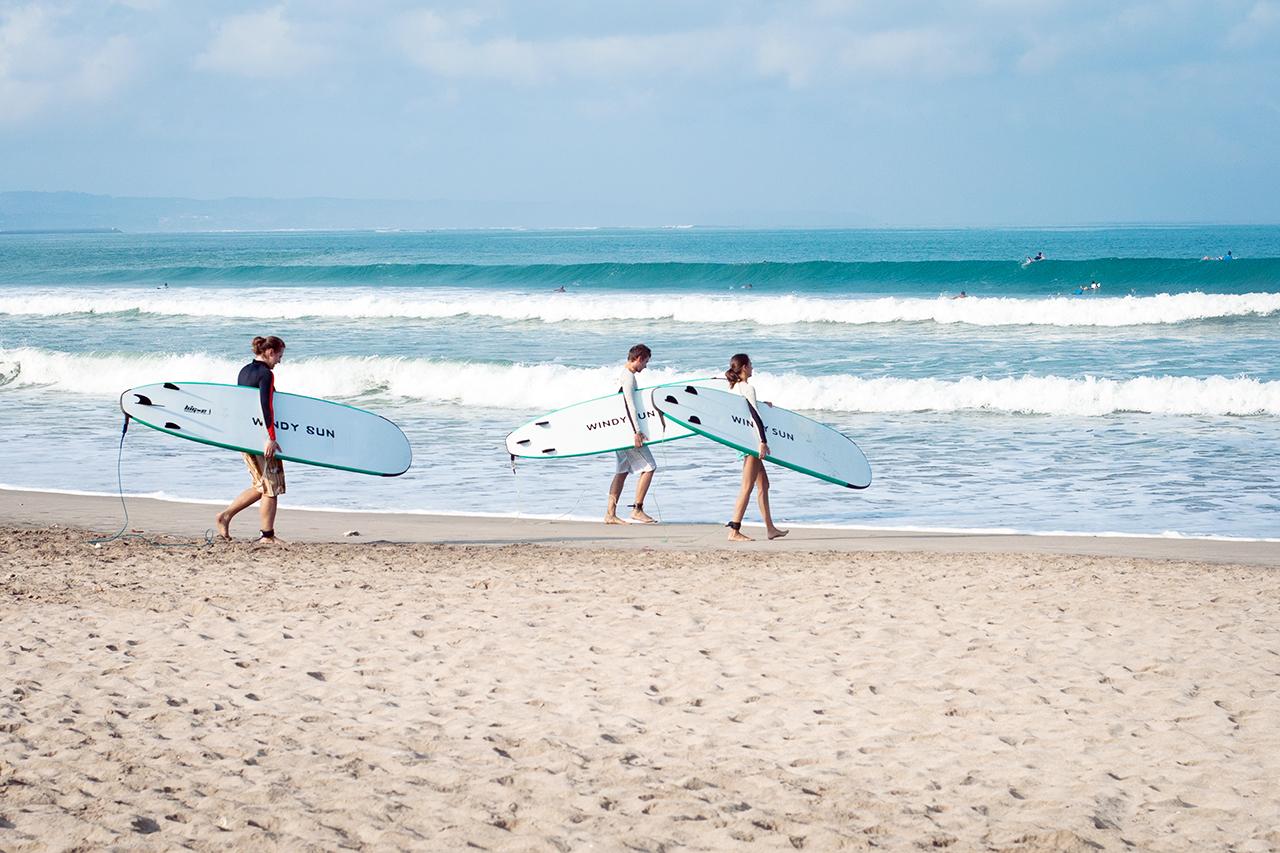 Начинающие серферы на пляже Куты, Бали, Индонезия