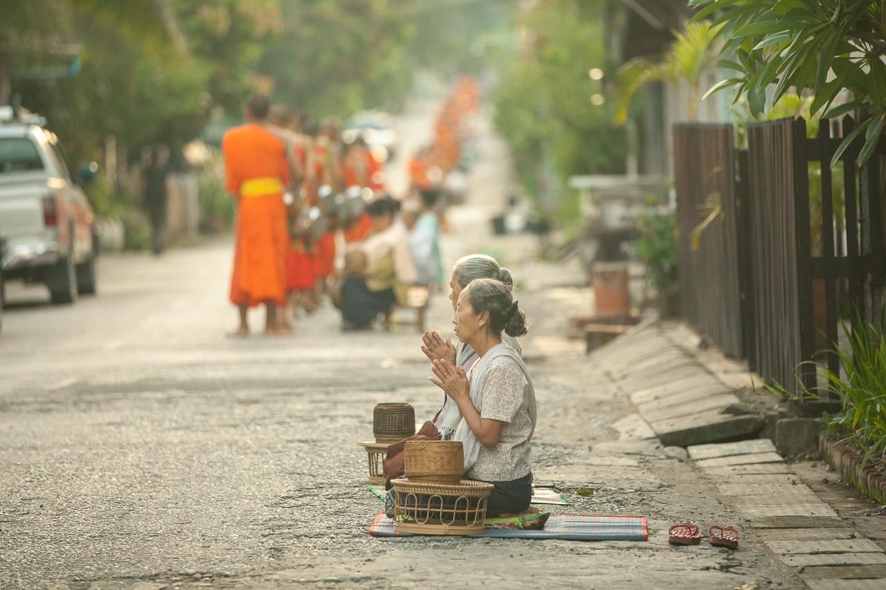 Путешествие по Лаосу: Женщины молятся после совершения подаяния